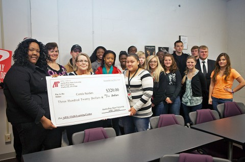 Students in the APSU 1000 class taught by Lynette Taylor present a ceremonial check November 14th to Connie Sanders (standing behind check in the middle), director of the APSU Child Learning Center, to help with playground improvements. (Photo by Jennifer Oliphant, APSU Public Relations and Marketing)