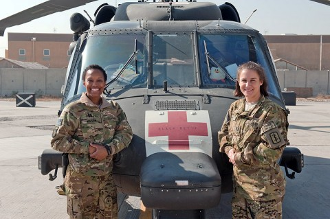 U.S. Army captains Nicole Nelson and Julie Duffy, enroute critical care nurses with 30th Medical Brigade, Task Force Med-A, attached to C Company, 6th Battalion, 101st Combat Aviation Brigade, Task Force Shadow, stand in front of their office, an HH-60M Black Hawk helicopter on Bagram Airfield, Afghanistan, Nov. 8, 2012. Duffy and Nelson bring critical care nursing skills to battlefield aeromedical evactuation assets of TF Shadow. (U.S. Army photo by Sgt. Duncan Brennan, 101st CAB PAO)