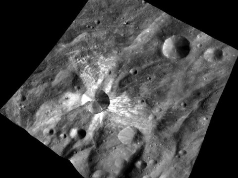 This image from NASA's Dawn spacecraft features the distinctive crater Canuleia on the giant asteroid Vesta. Canuleia, about 6 miles (10 kilometers) in diameter, is distinguished by the rays of bright material that streak out from it. (Image credit: NASA/JPL-Caltech/UCLA/MPS/DLR/PSI/Brown)
