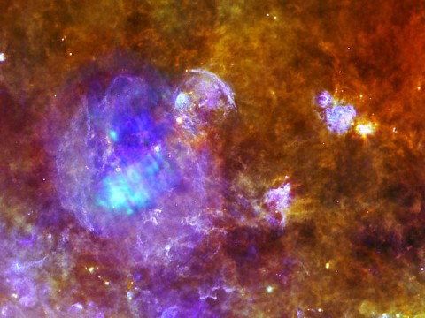 Supernova remnant W44 is the focus of this new image created by combining data from ESA's Herschel and XMM-Newton space observatories. W44 is the vast purple sphere that dominates the left hand side of this image, and measures about 100 light-years across. (Image credits: Herschel: Quang Nguyen Luong & F. Motte, HOBYS Key Program consortium, Herschel SPIRE/PACS/ESA consortia. XMM-Newton: ESA/XMM-Newton)