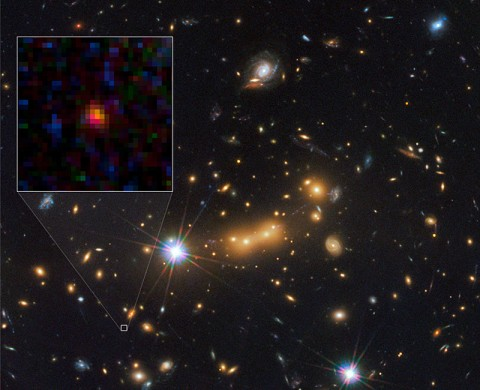 In this image, astronomers use NASA's Hubble Space Telescope and a cosmic zoom lens to uncover the farthest known galaxy in the universe. Observations from NASA's Spitzer Space Telescope helped confirm the finding. (Image credit: NASA/ESA/STScI/CLASH)