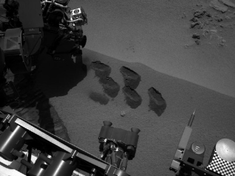 "NASA's Mars rover Curiosity used a mechanism on its robotic arm to dig up five scoopfuls of material from a patch of dusty sand called ""Rocknest,"" producing the five bite-mark pits visible in this image from the rover's left Navigation Camera (Navcam). Each of the pits is about 2 inches (5 centimeters) wide. (Image credit: NASA/JPL-Caltech)"