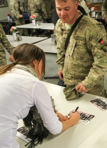 """Grammy award winning song writer Hillary Lindsey signs an autograph for Sgt. Brian Fogarty, a soldier assigned to Headquarters Troop, 1st Squadron, 33rd Cavalry Regiment, 3rd Brigade Combat Team """"Rakkasans,"""" 101st Airborne Division (Air Assault), during an autograph session by the Nashville to You Tour at Camp Clark, Nov. 15, 2012. The tour featured Nashville's top songwriters and performers as they traveled throughout Afghanistan performing for deployed soldiers. (U.S. Army Photo by Sgt. 1st Class Abram Pinnington, TF 3/101 PAO)"""