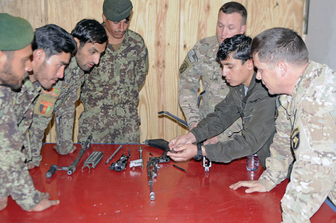 Afghan National Army soldiers from the 61st Kandak gather closely to view the different parts of an M240B machine this week on Combat Outpost Honikar-Miracle, Afghanistan. The instructors from Security Force Assistance Advisory Team 6, 2nd Battalion, 327th Infantry Regiment, 1st Brigade Combat Team, 101st Airborne Division used an interpreter to help explain the class and the names of each part. (U.S. Army photo by Sgt. Jon Heinrich, Task Force 1-101 PAO)