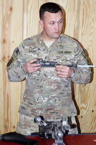 Sgt. Jason Sabin, a member of Security Force Assistance Advisory Team 6, 2nd Battalion, 327th Infantry Regiment, 1st Brigade Combat Team, 101st Airborne Division, holds the bolt carrier assembly of an M240B machine gun this week during a class on Combat Outpost Honikar-Miracle, Afghanistan.The class was given to Afghan National Army soldiers to instruct them on basic weapon skills so they could in turn teach their fellow soldiers what they learned. (U.S. Army photo by Sgt. Jon Heinrich, Task Force 1-101 PAO)