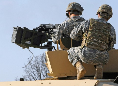 A range safety to the MK 19 grenade machine gun range shows a new Soldier the proper way to take aim with the mounted weapon system Nov.26 at Fort Campbell, Ky. The range gives Soldiers the opportunity to familiarize themselves with the weapon system for Individual Readiness Training in preparation for a deployment to Afghanistan. (U.S. Army photo taken by Sgt. Alan Graziano, 3rd Brigade Combat Team, 101st Airborne Division)