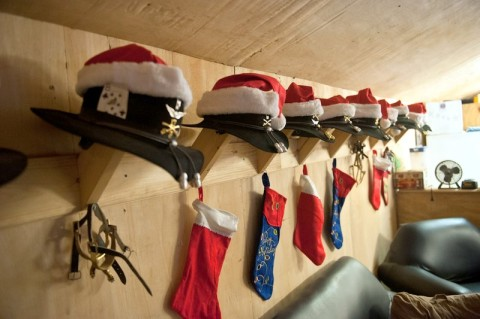 Stetsons adorned with Christmas hats and unit badges hang neatly in a row alongside spurs and stockings as the Yuletide season approaches at Forward Operating Base Fenty, Afghanistan. (U.S. Army photo by Sgt. Duncan Brennan, 101st CAB Public Affairs)