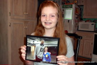 Kaitlan McLaughlin holding up a picture of herself taken with Anthony Davis.
