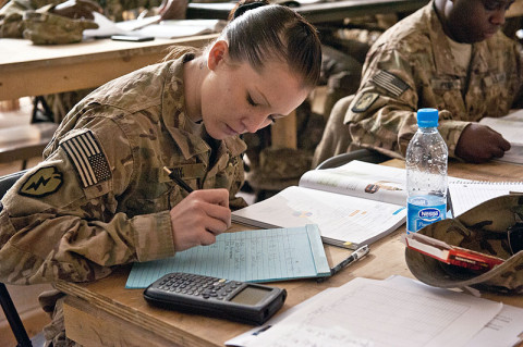 Spc. Amber Eddy, Headquarters and Headquarters company, 5th Battalion, 158th Aviation, aviation operations specialist, a native of Brigham City, Utah, takes notes and attempts to solve a problem posed to the the students during a class covering probability and statistics in a Task Force Ready classroom in Balkh province, Afghanistan, Nov. 14th. (U.S. Army photo by Sgt. Duncan Brennan, 101st CAB public affairs)