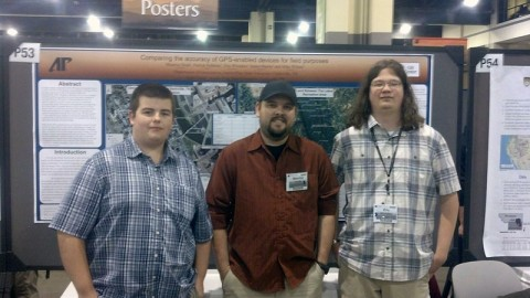 APSU students James Martin, Maurice Testa and Eric Whitaker stand before their poster at the Geological Society of America meeting.