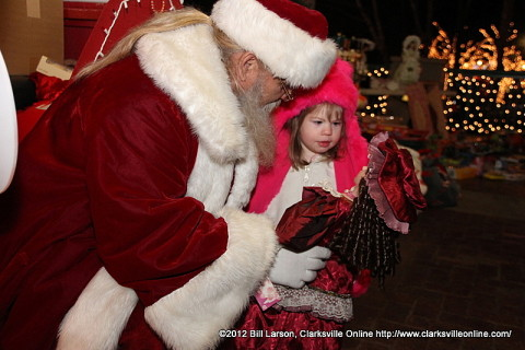 Santa gives a little girl a porcelain doll almost as big as she is