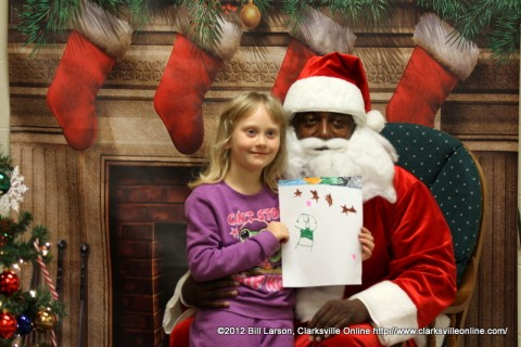 A young girl presents her Christmas drawing to Santa Claus