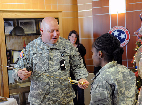 Maj. Gen. Max Haston, Tennessee's Adjutant General, presents Pfc. Zuri Walker with the ceremonial saber to cut the cake celebrating the 376th Birthday of the National Guard. (Photo by: Spc. Sterling Dailey)