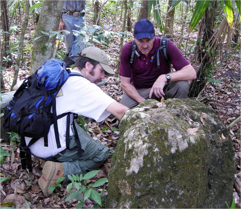 "Deep in the Guatemalan jungle, Sever and Griffin study a crumbled ""stele,"" a stone pyramid used by the Maya to record information or display ornately carved art. Sever and Griffin found the stele and other ruins hidden for more than 1,000 years during an expedition that relied on NASA remote-sensing technologies to pinpoint sites of ancient settlements. (NASA/Tom Sever)"
