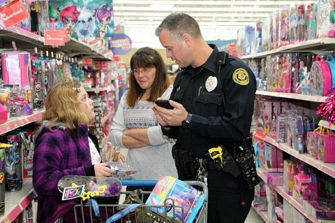 A Clarksville Police officer helps a young shopper keep a running talley of her purchases (Jim Knoll/Clarksville Police Department)