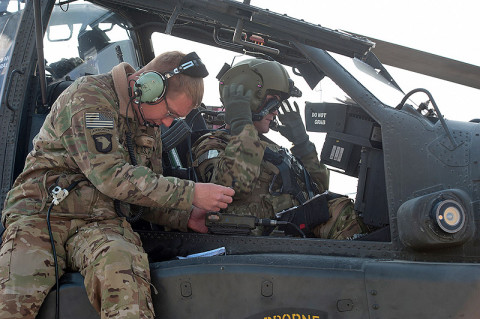 Spc. Marshall Miller, A Company, 1st Battalion, 101st Combat Aviation Brigade, AH-64 Apache helicopter crew chief, enters communication data into the systems of an AH-64 Apache helicopter during pre-flight checks at Forward Operating Base Salerno, Afghanistan, Jan. 16, 2013. (U.S. Army photo by Sgt. Duncan Brennan, 101st CAB public affairs)