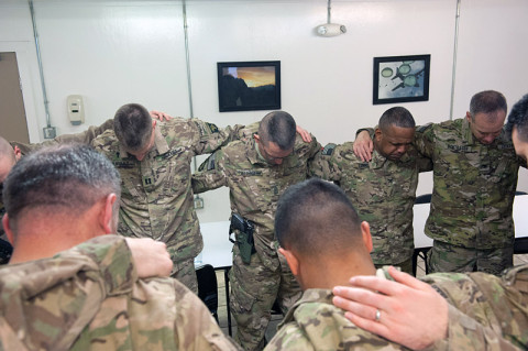 Soldiers conference huddle shoulder-to-shoulder in prayer at a breakfast concluding the 101st Combat Aviation Brigade, religious support team conference at Bagram Air Field, Afghanistan, Jan. 4th, 2013. (U.S. Army photo by Sgt. Duncan Brennan, 101st CAB public affairs)