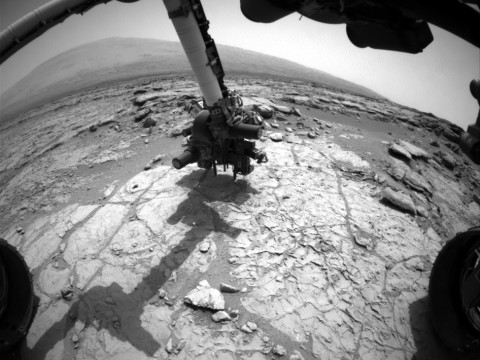 The percussion drill in the turret of tools at the end of the robotic arm of NASA's Mars rover Curiosity has been positioned in contact with the rock surface in this image from the rover's front Hazard-Avoidance Camera (Hazcam). (Image credit: NASA/JPL-Caltech)