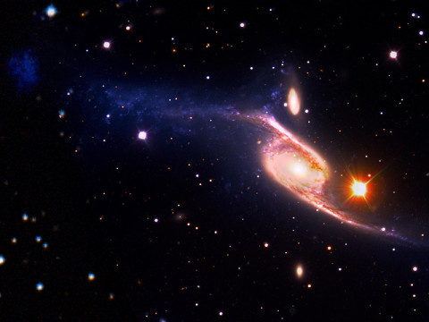 This composite of the giant barred spiral galaxy NGC 6872 combines visible light images from the European Southern Observatory's Very Large Telescope with far-ultraviolet (1,528 angstroms) data from NASA's GALEX and 3.6-micron infrared data acquired by NASA's Spitzer Space Telescope. (Image credit: NASA's Goddard Space Flight Center/ESO/JPL-Caltech/DSS)