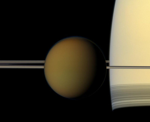 The colorful globe of Saturn's largest moon, Titan, passes in front of the planet and its rings in this true color snapshot from NASA's Cassini spacecraft. (Image credit: NASA/JPL-Caltech/Space Science Institute)