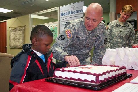 Blanchfield Army Community Hospital commander Col. Paul R. Cordts solicits the help from 5-year-old Justin Okoro to cut the cake February 1st during the kick-off to Patient Recognition Month at the hospital.