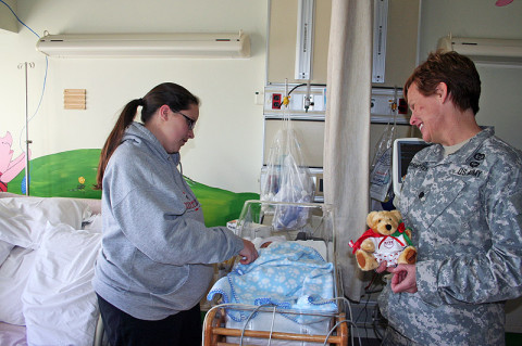Blanchfield Army Community Hospital Assistant Deputy Nurse Lt. Col. Sandra McNaughton makes an early Valentine Bear delivery February 1st to 11-day-old Walker Burkepile. Walker's mother, Stacey Burkepile, is staying in the hospital with Walker until he is well enough to go home. Twenty bears were donated by the Fort Campbell Better Opportunities Soldiers for BACH staff to hand out to patients during Patient Recognition Month.