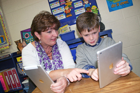 Second Grade Teacher, Frances Traughber works with Cooper Wallace on a spelling exercise using the iPad mini.