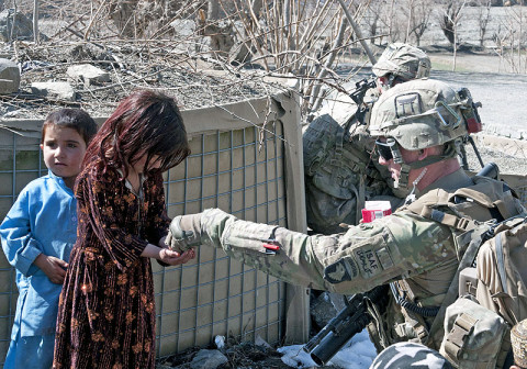 U.S. Army Sgt. Jason Finamore, a team leader with 3rd Platoon, Troop A, 1st Squadron, 33rd Cavalry Regiment, 3rd Brigade, 101st Airborne Division (Air Assault), hands out candy to Afghan children, Feb. 12, 2013, in Paktya Province, Afghanistan. The platoon conducted a joint patrol with the Afghan Uniformed Police. (U.S. Army photo by Spc. Alex Kirk Amen, 115th Mobile Public Affairs Detachment)