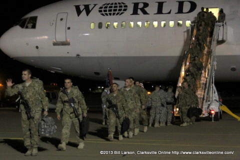 The returning soldiers disembark from the aircraft and head past their families to the hanger