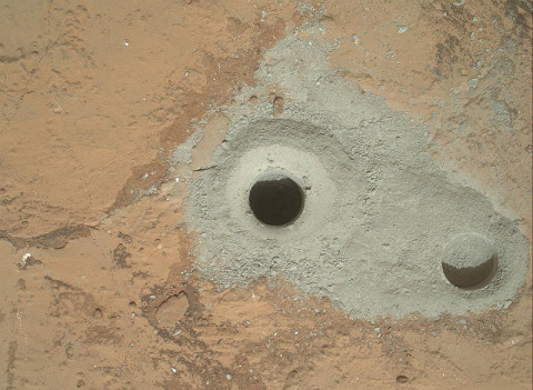 "At the center of this image from NASA's Curiosity rover is the hole in a rock called ""John Klein"" where the rover conducted its first sample drilling on Mars. The drilling took place on Feb. 8th, 2013, or Sol 182, Curiosity's 182nd Martian day of operations. Several preparatory activities with the drill preceded this operation, including a test that produced the shallower hole on the right two days earlier, but the deeper hole resulted from the first use of the drill for rock sample collection. (Image credit: NASA/JPL-Caltech/MSSS)"
