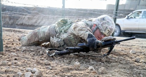 """Staff Sgt. Robert Dodge, a cavalry scout assigned to Troop B, 1st Squadron, 33rd Cavalry Regiment, 3rd Brigade Combat Team """"Rakkasans,"""" 101st Airborne Division (Air Assault), low crawls under barbed wire during the obstacle course portion of the brigade noncommissioned officer and Soldier of the quarter competition on Forward Operating Base Salerno, Afghanistan, Feb. 15, 2013. Competitors were timed on performing a five mile road march as well as complete five stations throughout the competition. (U.S. Army photo by Spc. Brian Smith-Dutton, Task Force 3/101 Public Affairs)"""
