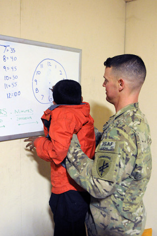 U.S. Army Spc. Michael Schmidt, a civil affairs specialist with 450th Civil Affairs Battalion, Provincial Reconstruction Team Nangarhar, 1st Brigade Combat Team, 101st Airborne Division, and native to Flint, MI, holds a young student up so he can draw on a clock Feb. 16, 2013, during Boy's English Class at Forward Operating Base Finley-Shields, Afghanistan. (U.S. Army photo by Sgt. Jon Heinrich, Task Force 1-101 PAO)