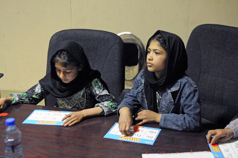 Local Afghan girls play a game of alphabet bingo to help learn English letters Feb. 15, 2013, during Girl's English Class at Forward Operating Base Finley-Shields, Afghanistan. The children are part of a volunteer-run program to help teach local children language skills. (U.S. Army photo by Sgt. Jon Heinrich, Task Force 1-101 PAO)