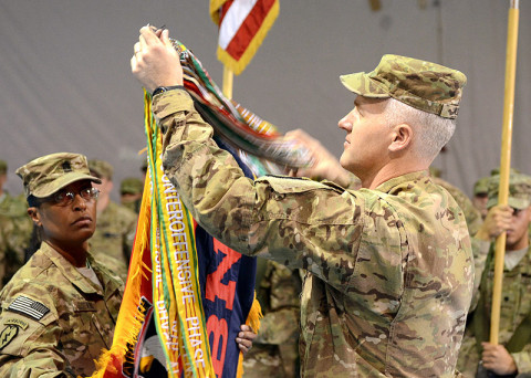 U.S. Army Command Sgt. Maj. Tonika Scott-Morris (left), and Lt. Col. Scott Noon, Division Headquarters and Headquarters Battalion, 101st Airborne Division (Air Assault) command team, uncase the unit flag during the casing ceremony for the division headquarters battalion for the outgoing 1st Infantry Division and the uncasing ceremony for the division headquarters battalion for the incoming 101st Airborne Division (Air Assault), Feb. 28, 2013, at Bagram Airfield.  (U.S. Army photo by Sgt. 1st Class Kevin Hartman, 115th Mobile Public Affairs Detachment)