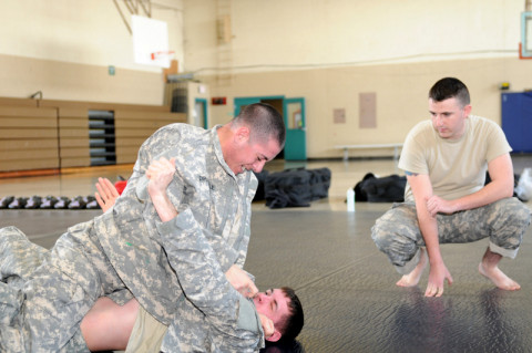 Spc. Billy Robertson, a military police with the 561st Military Police Company, 101st Sustainment Brigade, 101st Airborne Division (Air Assault), observes Spc. Louis Dipasquale an MP (top) and Spc. Dylan Rutherford a mechanic (bottom), both with the MP Company, while they practice combative moves during combative level II training course, March 15, at the Lozada Physical Fitness Center here at Fort Campbell. (Sgt. Sinthia Rosario/U.S. Army)