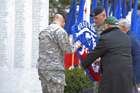 """From left to right: Maj. John Page and 1st Sgt. Jeremy Clark, the Rear-Detachment Command Group of the 3rd Brigade Combat Team """"Rakkasans,"""" 101st Airborne Division (Air Assault), Irving Weinsoff, president of the 187th National Rakkasan Association, and retired Command Sgt. Maj. James Musgrove, former regimental command sergeant major, carry the 187th Infantry Regimental Crest and place it in front of the Regimental Pylon at an activation ceremony Feb. 20 at Fort Campbell, KY. (U.S. Army photo taken by Sgt. Alan Graziano, 3rd Brigade Combat Team, 101st Airborne Division)"""