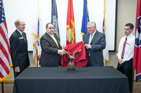 Dr. Lowell Roddy (from left), APSU Student Veterans Organization adviser, SVA President Michael Cleveland, APSU President Hall and Military Student Center Coordinator Justin Machain unveil the national award from the Student Veterans of America during a ceremony held Monday, March 18th. (Photo by Beth Liggett, APSU photographer)