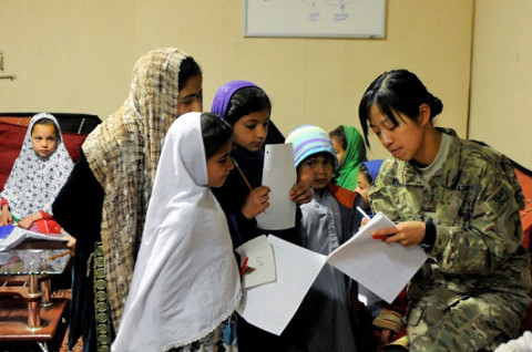U.S. Army Spc. Gamei Kwong, 414th Civil Affairs Battalion, teaches Afghan children English.