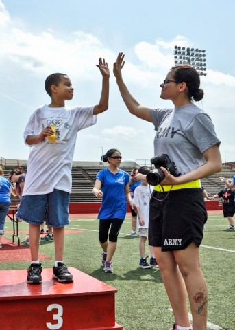 Spc. Angela Tedeski, a medic with Company C, 526th Brigade Support Battalion, 2nd Brigade Combat Team, 101st Airborne Division (Air Assault), congratulates students from Fort Campbell's Barsanti Elementary School as they receive their placement ribbons during the Area 12 Special Olympics, held at Clarksville's Austin Peay Stadium on April 18. (US Army photo by Sgt. Keith Rogers, 2nd BCT UPAR, 101st Abn. Div.)