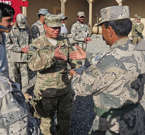 """Army Sgt. Luciano Mada, a medic assigned to Headquarters, Headquarters Company, 3rd Battalion, 187th Infantry Regiment, 3rd Brigade Combat Team """"Rakkasans,"""" 101st Airborne Division (Air Assault), shakes hands with an Afghan Border Policeman during their graduation ceremony of his medical course at Forward Operating Base Salerno, Afghanistan. (Courtesy Photo)"""