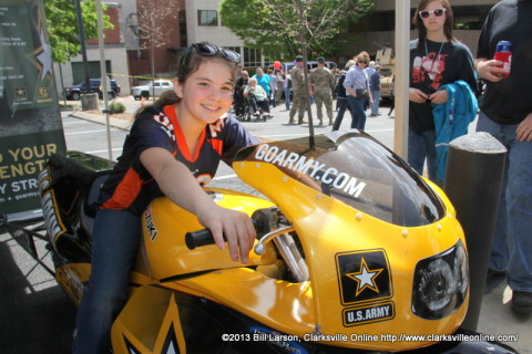 A young lady gets to sit on the Go Army Bike in the USAA Military Appreciation area