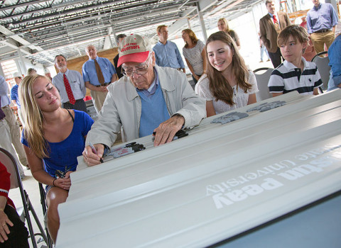 James Maynard — the first to sign during Tuesday's topping-off ceremony at the Maynard Mathematics and Computer Science Building at APSU — is surrounded by some of his grandchildren. (Photo by Beth Liggett, APSU photographer)