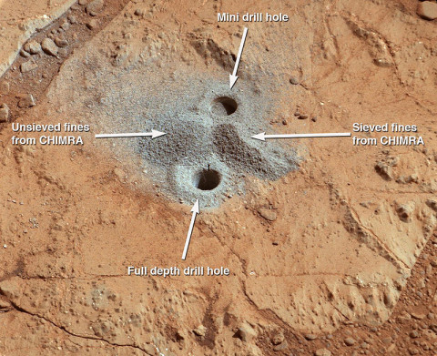 This image shows the first holes into rock drilled by NASA's Mars rover Curiosity, with drill tailings around the holes plus piles of powdered rock collected from the deeper hole and later discarded after other portions of the sample had been delivered to analytical instruments inside the rover. (NASA/JPL-Caltech/MSSS)