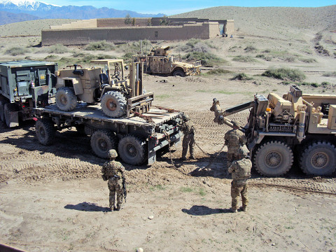 U.S. Army Soldiers, Sgt. James Kendall and Spc. Peter Brousseau, 426th Brigade Support Battalion, 1st Brigade Combat Team, 101st Airborne Division (Air Assault), attach chains to the back of an M1120 HEMTT Load Handling System in order to recover the vehicle from a sinkhole. (U.S. Army photo by 1st Lt. Lisa Maginot, 426th BSB Unit Public Affairs Representative)