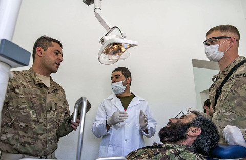 "U.S. Army Sgt. Brian Kavanagh, a radiology specialist, Company C, 626th Brigade Support Battalion, 3rd Brigade Combat Team ""Rakkasans,"" 101st Airborne Division (Air Assault), consults with Afghan National Army Dentist Cpt. Mirwais Hussaini, 1st Brigade, 203rd Corps, through the use of an interpreter at Camp Parsa, April 14, 2013. The procedure was part of an ongoing partnership between ANA and U.S. Army medical personnel for ANA troops. (U.S. Army National Guard photo by Sgt. Joshua S. Edwards, 129th Mobile Public Affairs Detachment)"