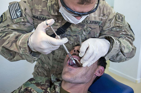 """U.S. Army Sgt. Brian Kavanagh, a radiology specialist, Company C, 626th Brigade Support Battalion, 3rd Brigade Combat Team """"Rakkasans,"""" 101st Airborne Division (Air Assault), injects a numbing agent into the mouth of an Afghan National Army Soldier at Camp Parsa, April 14, 2013. The procedure was part of an ongoing partnership between ANA and U.S. Army medical personnel for ANA troops. (U.S. Army National Guard photo by Sgt. Joshua S. Edwards, 129th Mobile Public Affairs Detachment)"""