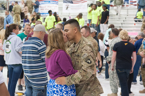 Spc. Ross Michael Noffisinger, Headquarters and Headquarters Company, 1st Battalion, 101st Combat Aviation Brigade, 101st Airborne Division (Air Assault), kisses his wife during a welcome home ceremony at Fort Campbell, KY, May 14th, 2013. (U.S. Army photo by Sgt. Duncan Brennan, 101st CAB Public Affairs)