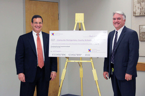 Schools Director B.J. Worthington accepts a $1.6 million grant from Gregg Fleisher, chief program officer for the National Math and Science Initiative.