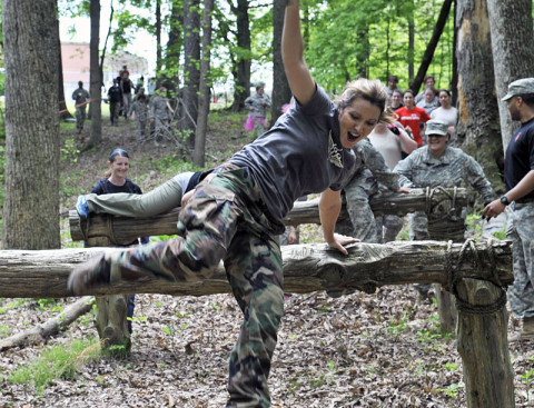 A spouse of a 1st Battalion, 160th Special Operations Aviation Regiment (Airborne) Soldier soars over the gut buster logs during the Pink Platoon event May 2, 2013, at Fort Campbell, Ky. (Photo by Staff Sgt. Rick Branch, 160th SOAR (A) Public Affairs)