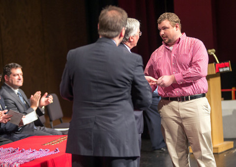 APSU President Tim Hall presents graduate and veteran Darrell Sheffield with an APSU military coin. (Photo by Beth Liggett/APSU).